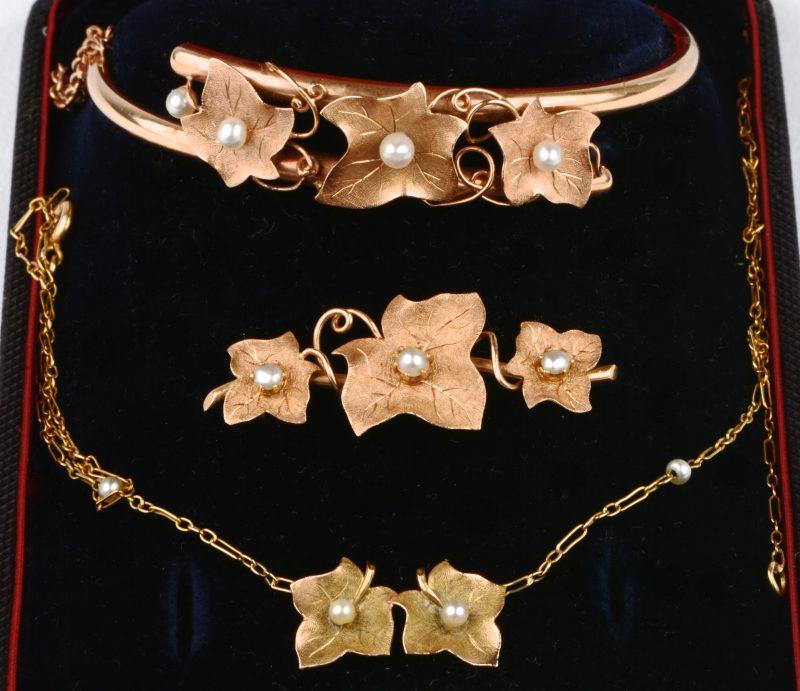 Een 18 karaats geel gouden armband, broche en ketting met hanger in blad vorm bezet met pareltjes. In etui.