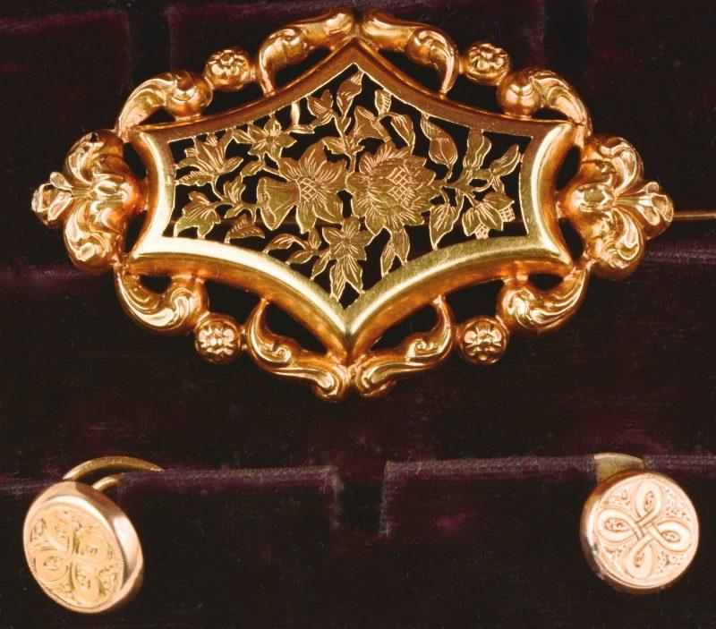 Een 18 karaats geel gouden broche met ajourwerk in de vorm van bloemen en twee knoopversieringen.
