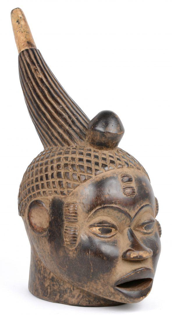 Een Afrikaans houten masker in de vorm van een vrouwenhoofd.