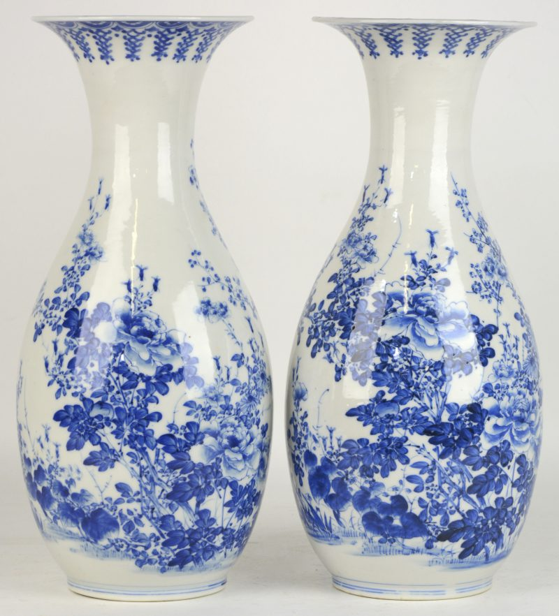 Een paar kraagvazen van blauw en wit Chinees porselein, versierd met een decor van bloesems. Eén met restauratie.
