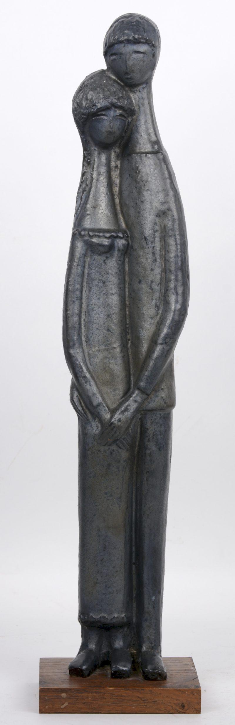 """""""Koppel"""". Een beeld grijsgeglazuurd aardewerk op houten sokkel."""