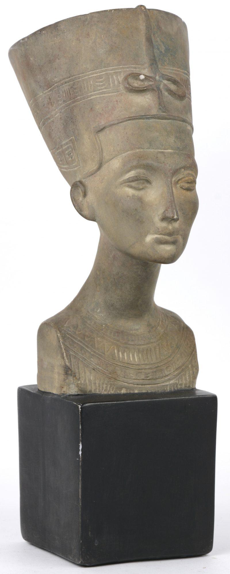Een buste van Nefertiti van grijsgepatineerd gips. Een schilfer bovenaan.