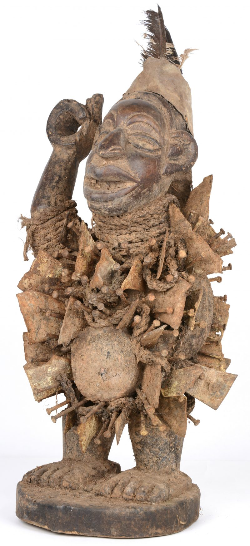 Een Afrikaans fetisjbeeld van gebeeldhouwd hout met metalen platen en nagels en bovenaan getooid met veren.