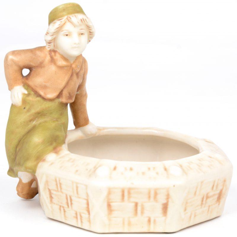 Een asbak van meerkleurig porselein in de vorm van een jongetje bij een mand. Onderaan gemerkt.