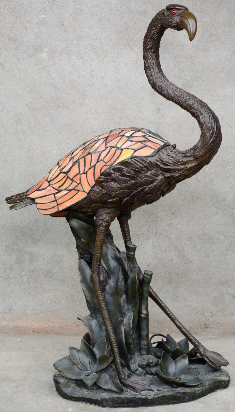 Een lamp van bruingepatineerd kunststof in de vorm van een Flamingo met vleugels van glas in lood als kap.