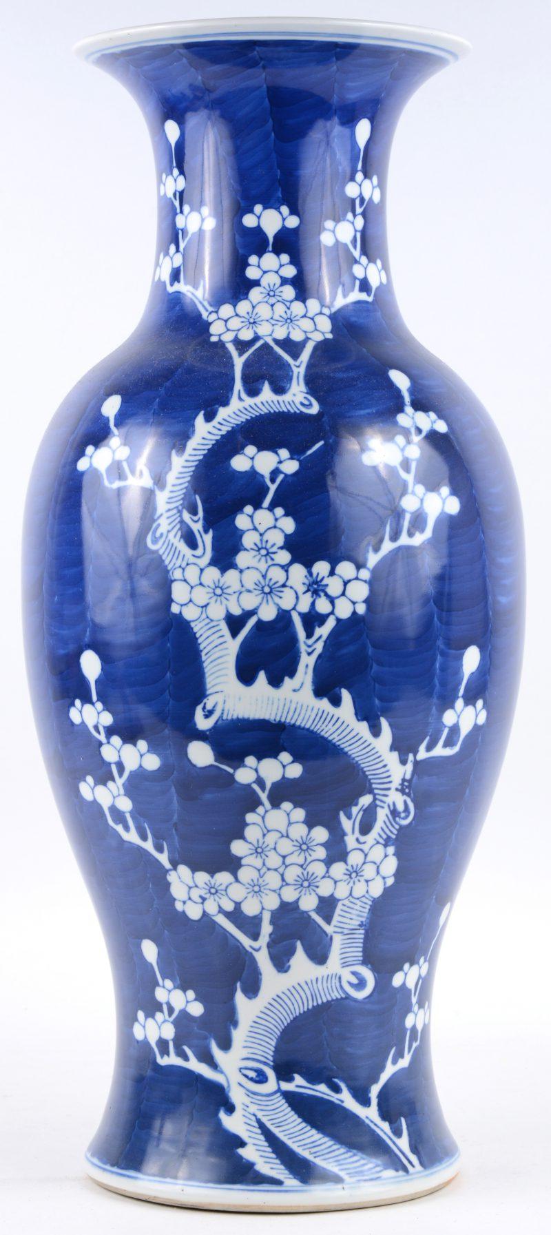 Een balustervaas van Chinees porselein met een wit op blauw decor van een bloeiende struik. Onderaan gemerkt: Zhongguo Jingdezhen Zhi.