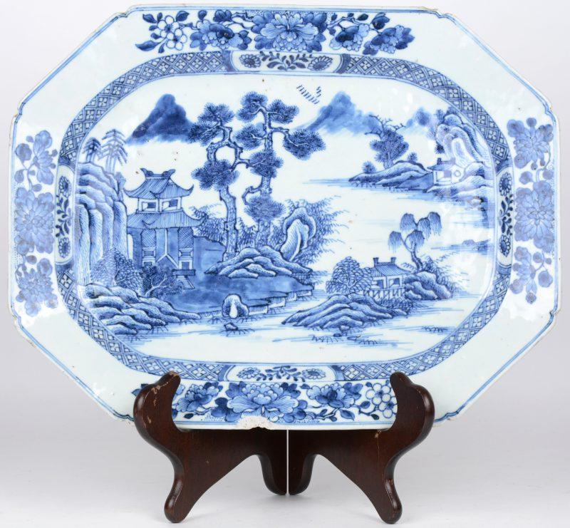 Een achthoekige schotel van Chinees porselein met een blauw op wit landschapsdecor. Schilfer.