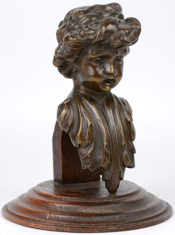 """""""Kinderkopje"""". Een bronzen ornament op houten sokkel."""