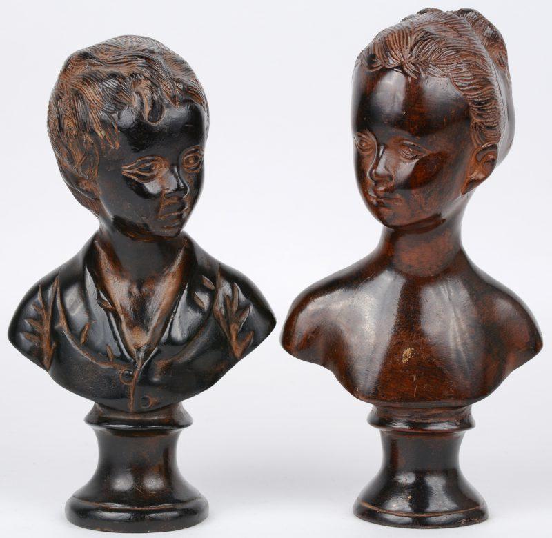 Een jongens- en en meisjesbuste van bruingepatineerd brons.