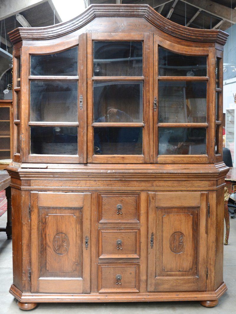 """Een tweeledige Duitse vitrinekast van eikenhout met onderaan twee paneeldeuren naast drie laden. In de paneeldeuren de initialen """"JC"""" & """"WR"""" en gedateerd 1817."""