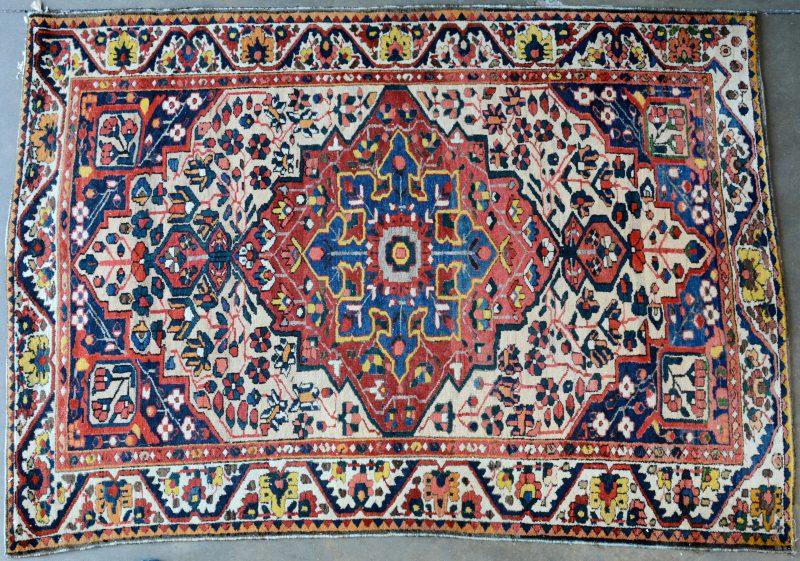 Een handgeknoopt Perzisch wollen karpet met een centraal motief.