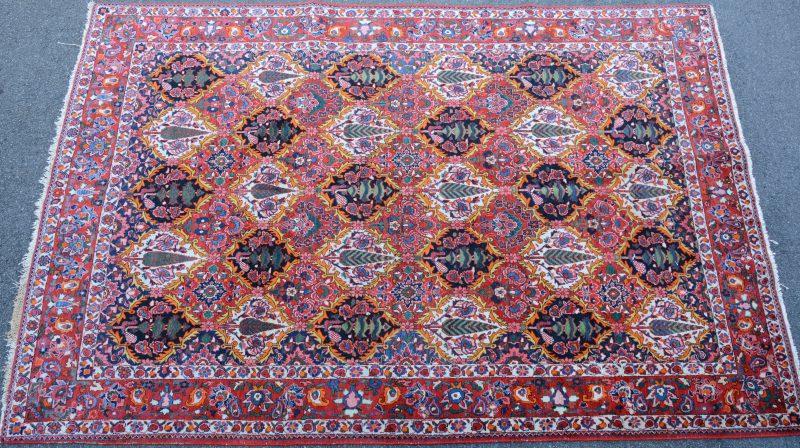 Een handgeknoopt Perzisch wollen tapijt met een decor van bomen.