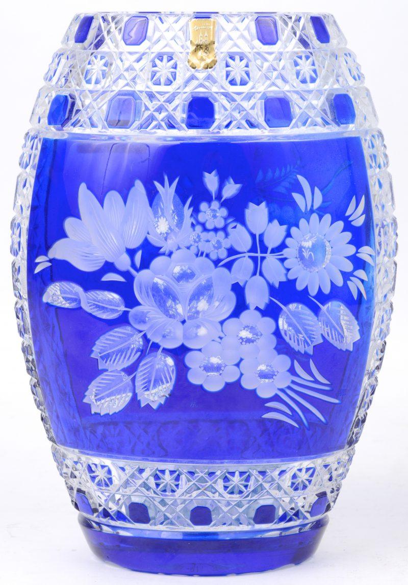 Een vaas van geslepen kleurloos en blauw kristal, versierd met een bloemendecor.