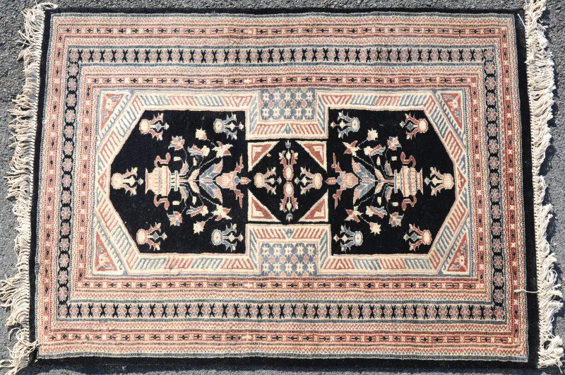 Een handgeknoopt Oosters wollen karpetje met een decor van bloemenvazen op zwarte achtergrond.