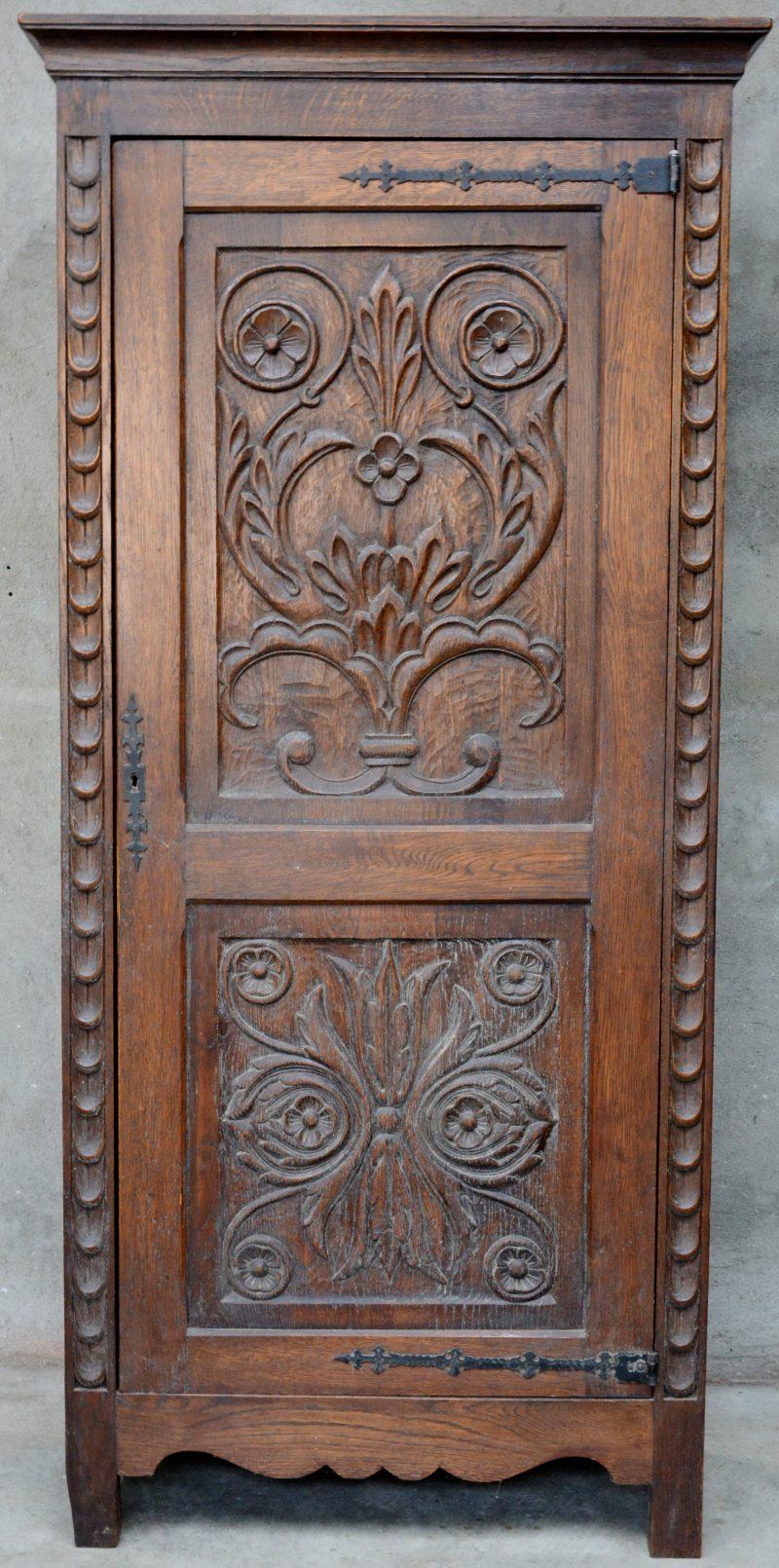 Een eikenhouten broodkast met een gesculpteerde deur.