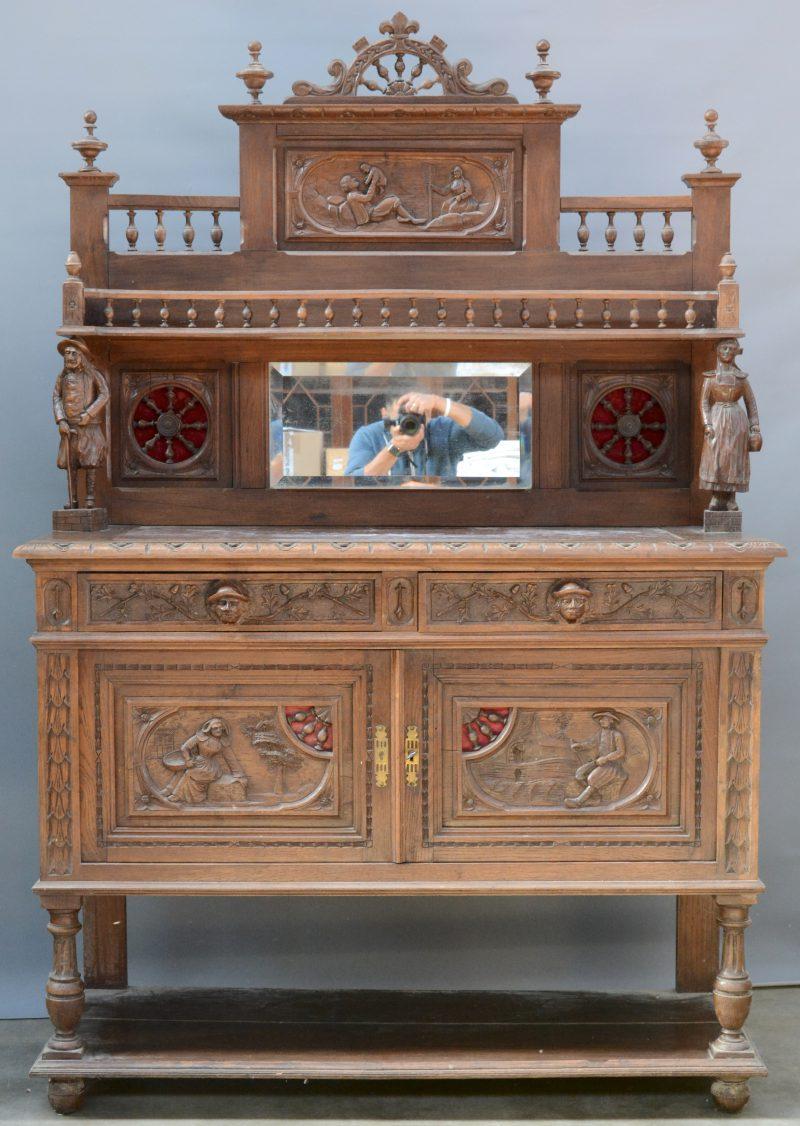 Een eikenhouten buffetkast met opzet, gedragen door twee gebeeldhouwde figuren. In het opzet een spiegel tussen twee wielen en bovenaan een galerijtje. Onderaan twee deuren en twee laden en een marmeren blad.