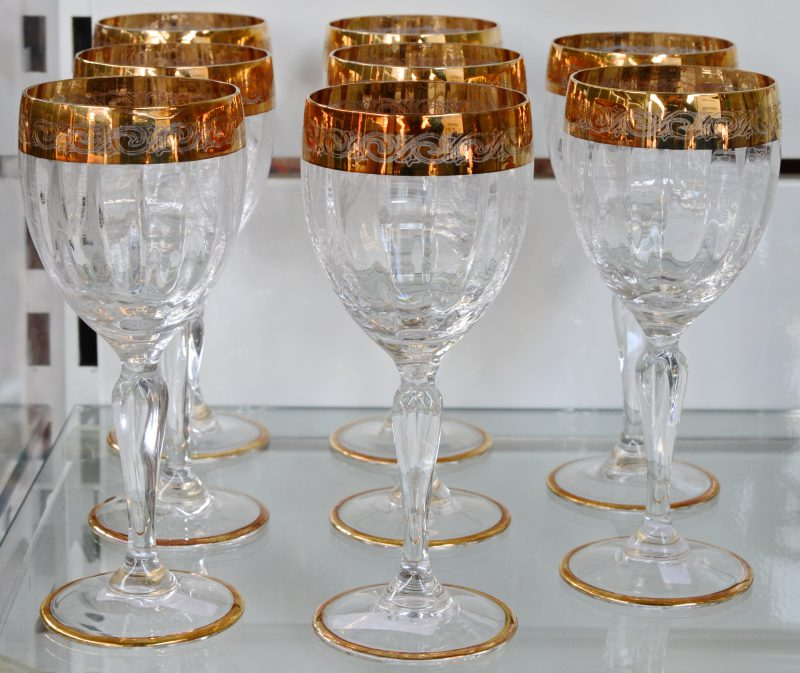 Een reeks van acht kristallen glazen met een geslepen en verguld decor. Murano.