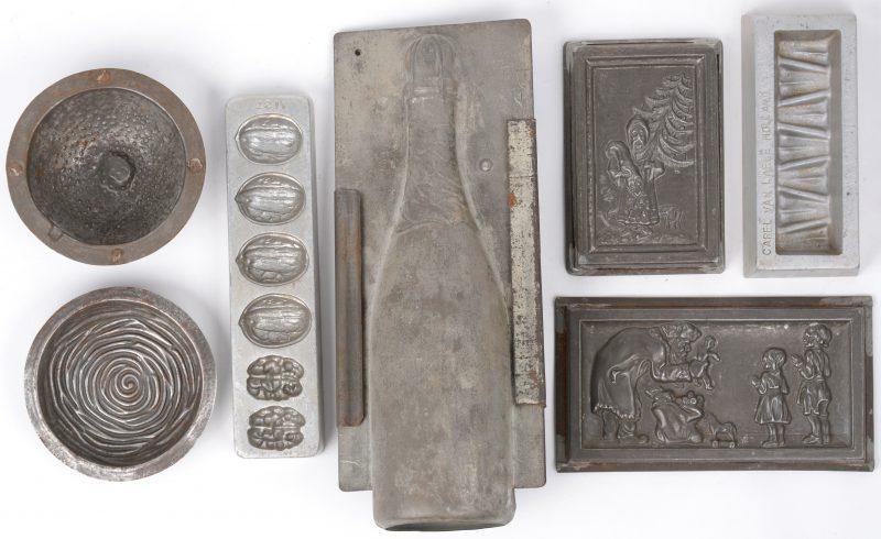 Een lot van zeven oude metalen chocoladevormen.