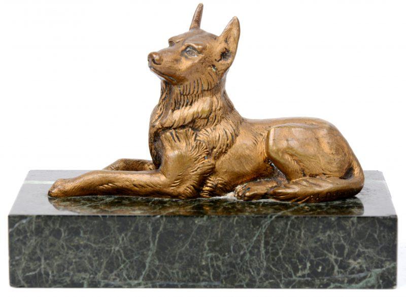 """""""Liggende hond"""". Een bronzen beeldje op groen marmeren sokkel."""