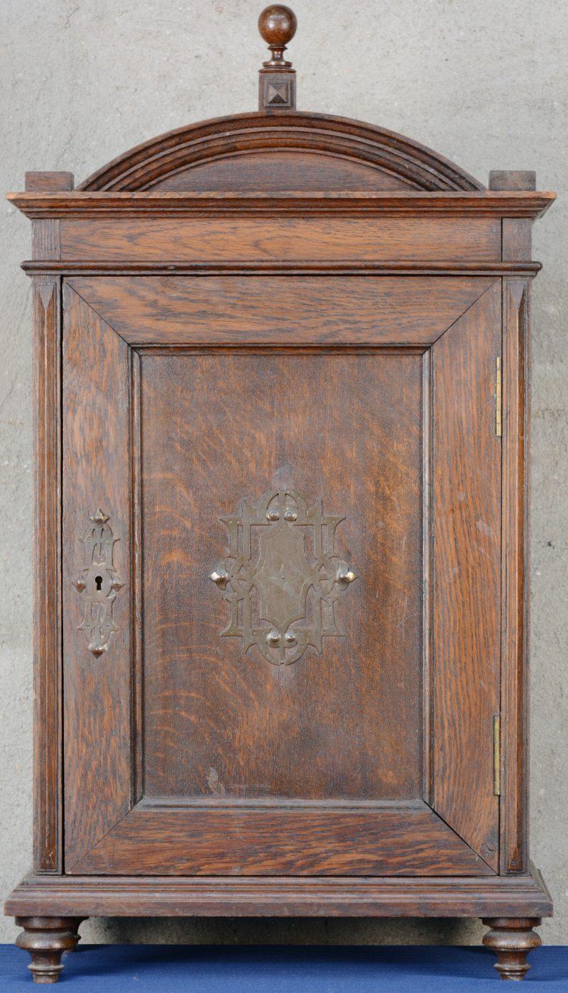 Een klein eikenhouten wandkabinetje met één deurtje met koperen versiering en met twee kleine laden binnenin.
