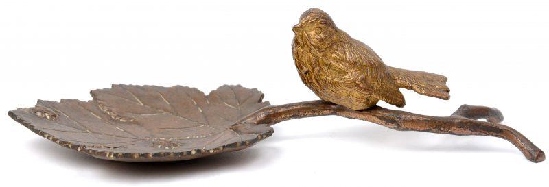 Een bronzen vide-poche in de vorm van een vogeltje op een blad. Met inscriptie 1927  - 1952.