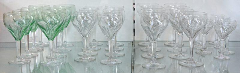 Een glazenservies van geslepen kristal in vier formaten, waarbij een model met groene kelk. +/- 30 stuks.