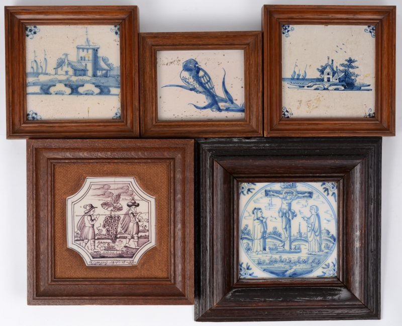 Een lot van vijf ingekaderde Delftse tegels met verschillende decors, waarbij vier in blauw en één in mauve. XIXe eeuw.