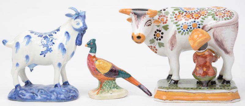 Een lot van drie diertjes van meerkleurig aardewerk van Makkum, bestaande uit een meerkleurige koe, een fazant en een een geit in blauw-wit. De laatste met een ontbrekende hoorn.
