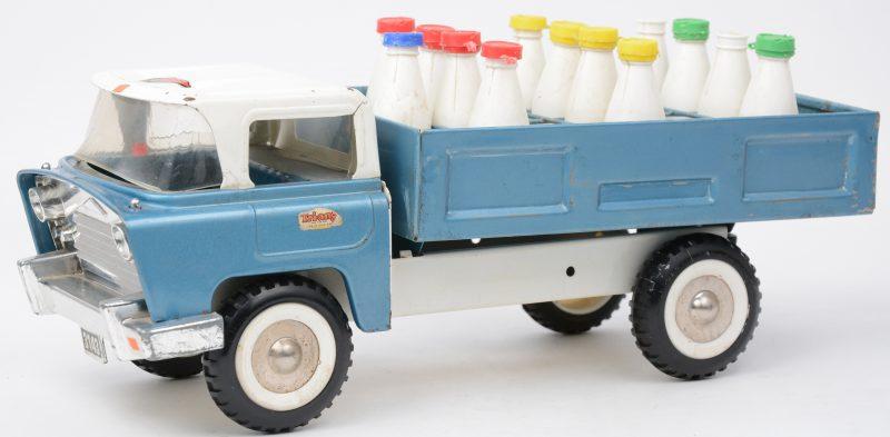 Een blikken speelgoedmelkwagen met negen plastic melkflesjes. Jaren '60.