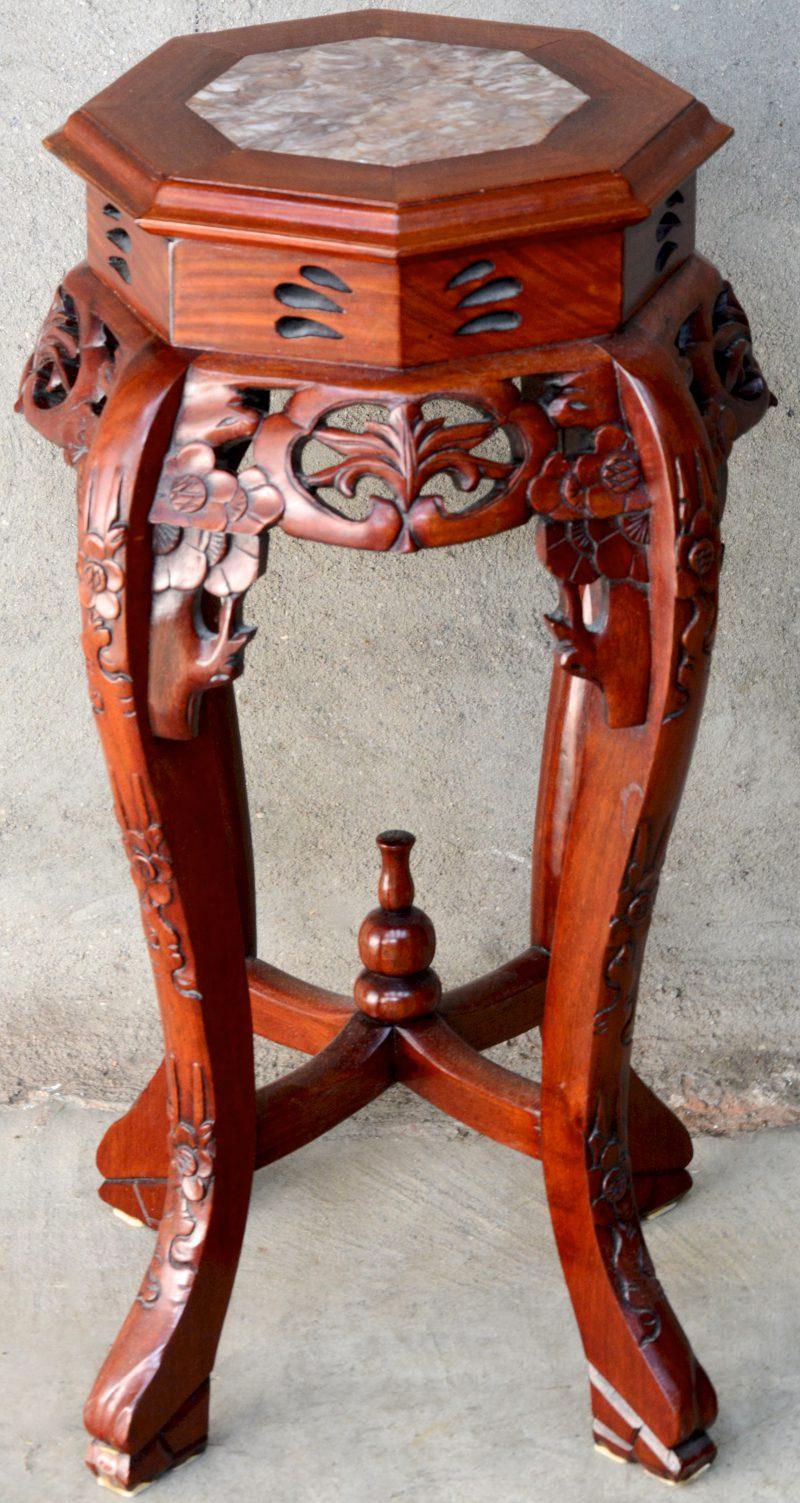Een piedestal van Chinees hardhout met marmeren blad.