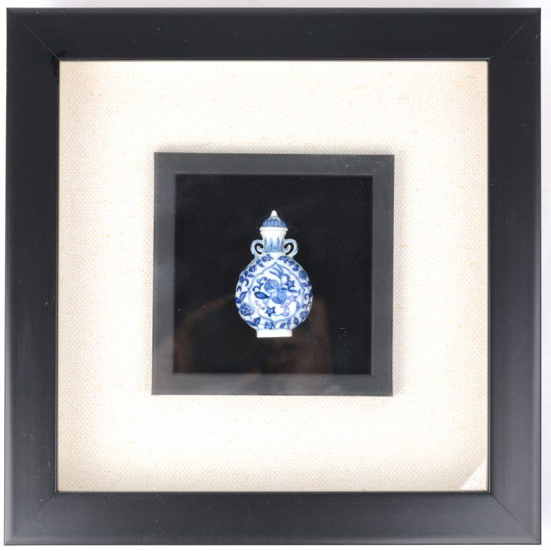 Een klein flesvaasje met deksel van blauw en wit Chinees porselein. Onderaan gemerkt. In kader achter glas.