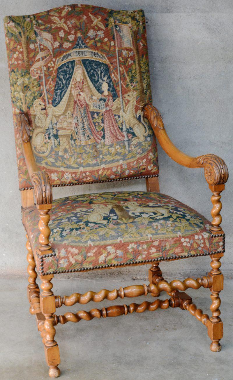 Een eikenhouten armstoel in Louis XIII stijl met getorste poten en bekleed met tapisserie.