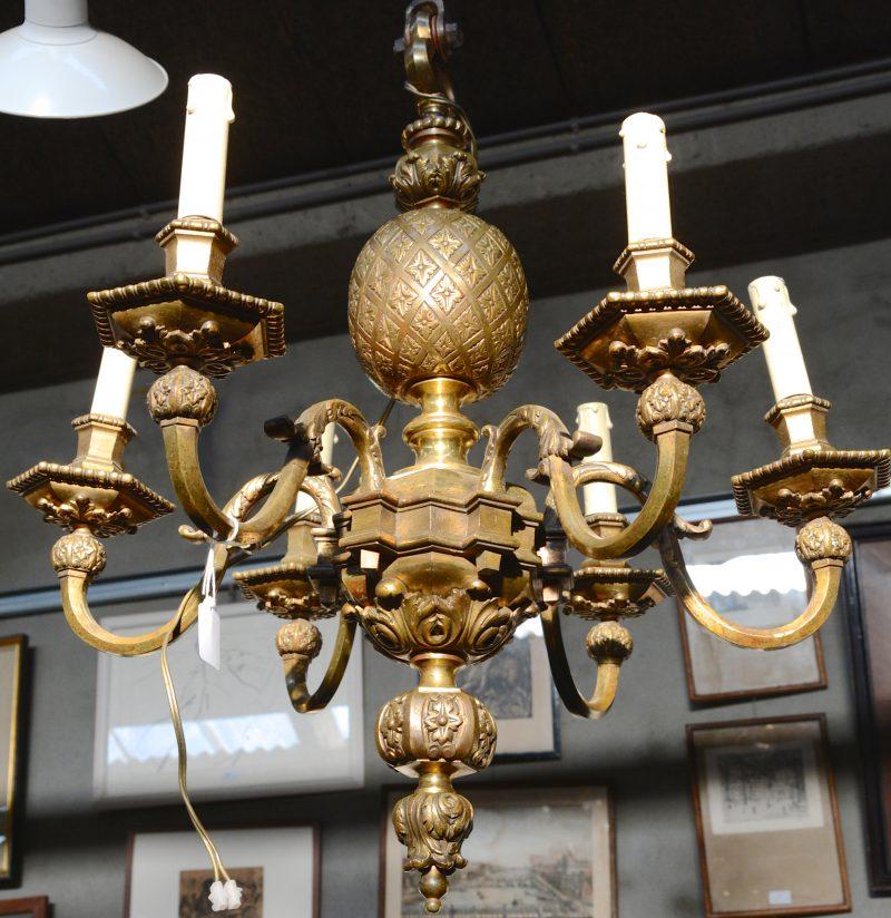Een bronzen luchter met zes lichtpunten.