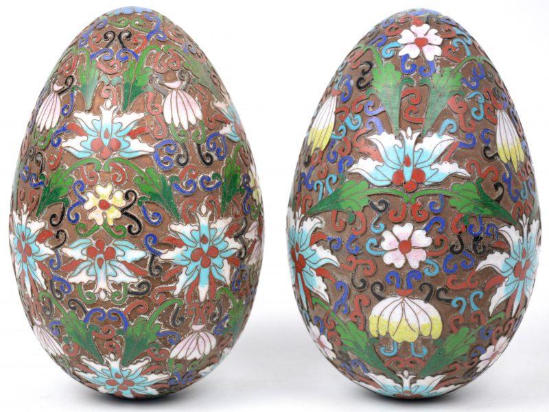 Een paar eieren van cloisonné op rood koper met een bloemendecor.