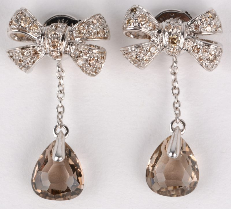 Een paar wit gouden strikvormige oorbellen bezet met briljanten met een gezamenlijk gewicht van ± 0,70 ct. en topaas.