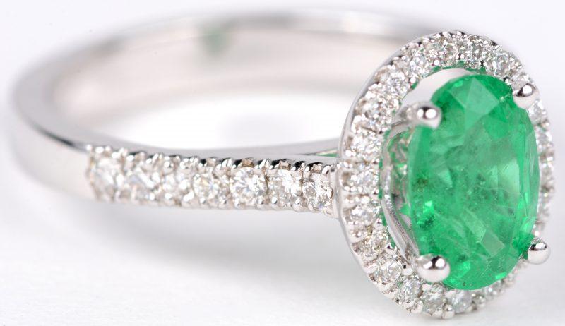 Een 18 karaats wit gouden ring bezet met diamanten met een gezamenlijk gewicht van ± 0,40 ct. en een centrale smaragd van ± 1,36 ct.