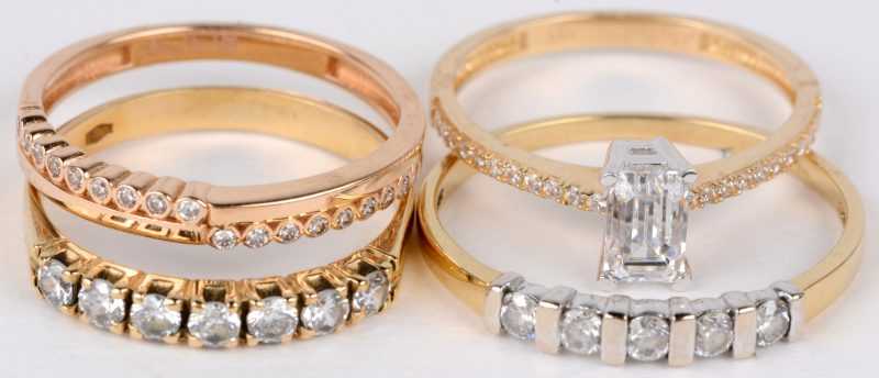 Vier verschillende 18 karaats geel gouden ringen bezet met fantasiestenen.