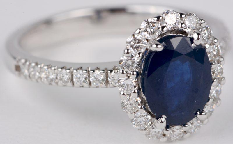 Een 18 karaats wit gouden ring bezet met diamanten met een gezamenlijk gewicht van ± 0,56 ct. en een centrale saffier van ± 1,40 ct.