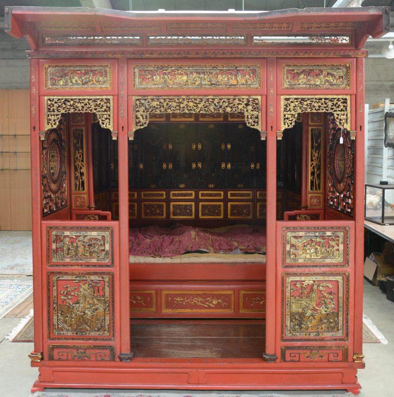 Een antiek Chinees bed van roodgelakt hout met vergulde versieringen. Binnenin schilderingen op zijde rondom en in de baldakijn. Enkele beschadigingen en manco's. XIXe eeuw.