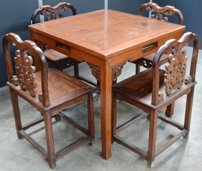 Een Chinese tafel met vier bijpassende stoelen van gesculpteerd tropisch hout.