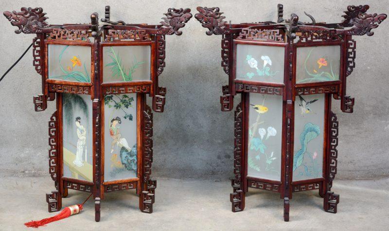 Een paar zeshoekige Chinese lantaarns van hout en glas, waarbij één met een decor van personages en één met vogels op bloeiende takken.