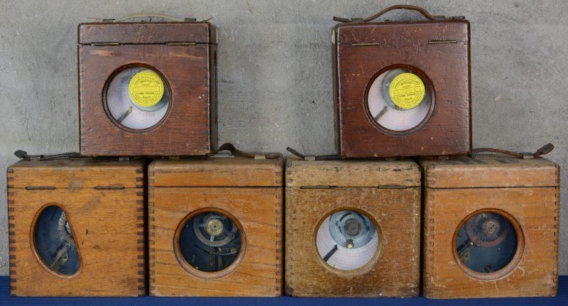 Zes oude constateurs voor de duivensport in houten kast.