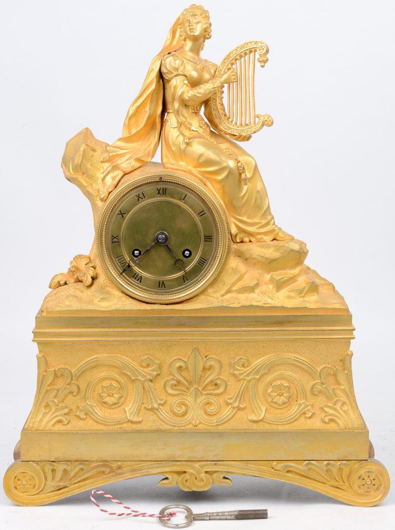 Een schouwpendule van verguld koper, getooid met een harpspelende jonge vrouw. Met slinger en sleutel.