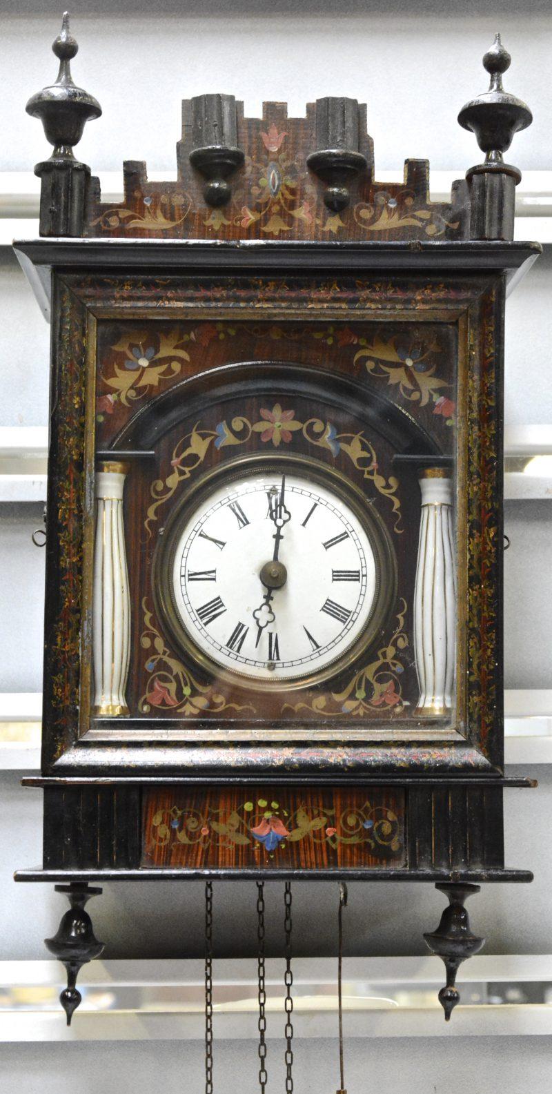 Een klokje van gepolychromeerd hout met een geëmailleerde wijzerplaat, geflankeerd door twee porseleinen zuiltjes. Met gewicht en slinger.