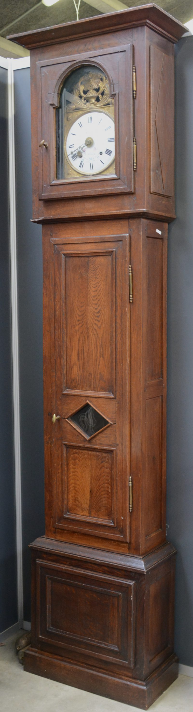 Een eikenhouten staande klok. Het werk met gedreven geel koper en geëmailleerde wijzerplaat. Eind XIXe eeuw.