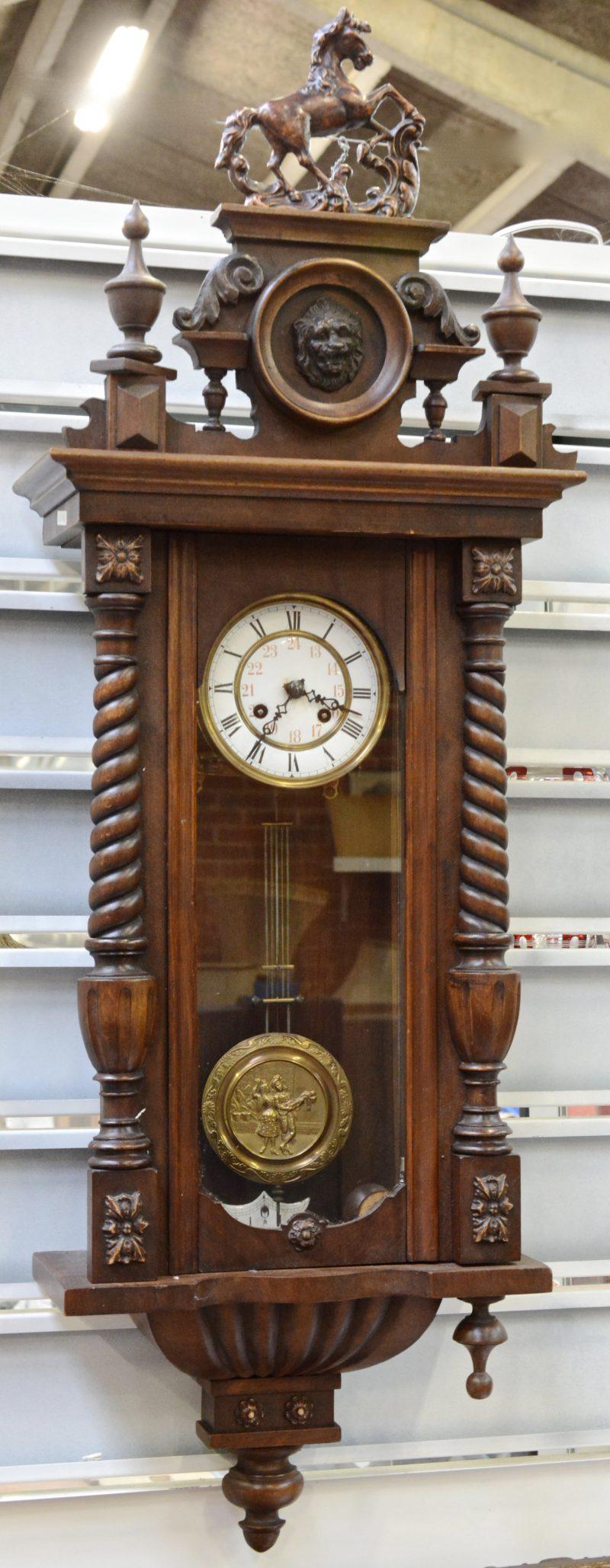 Een houten regulateur, bovenaan gesierd met een paard.