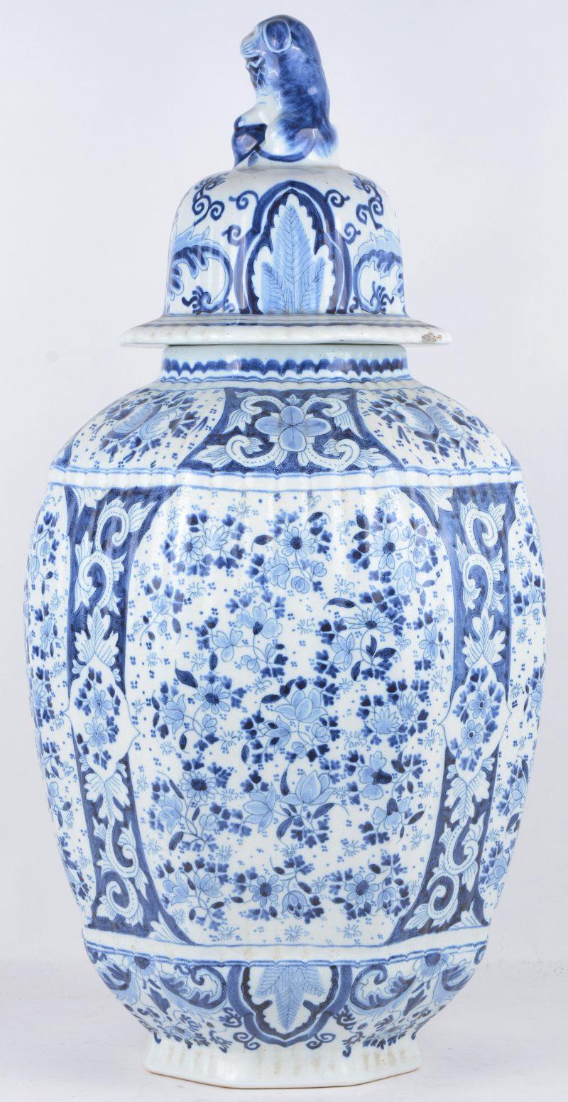 Een achthoekige dekselvaas van blauw en wit Delfts aardewerk, het deksel getooid met een zittende tempelleeuw.