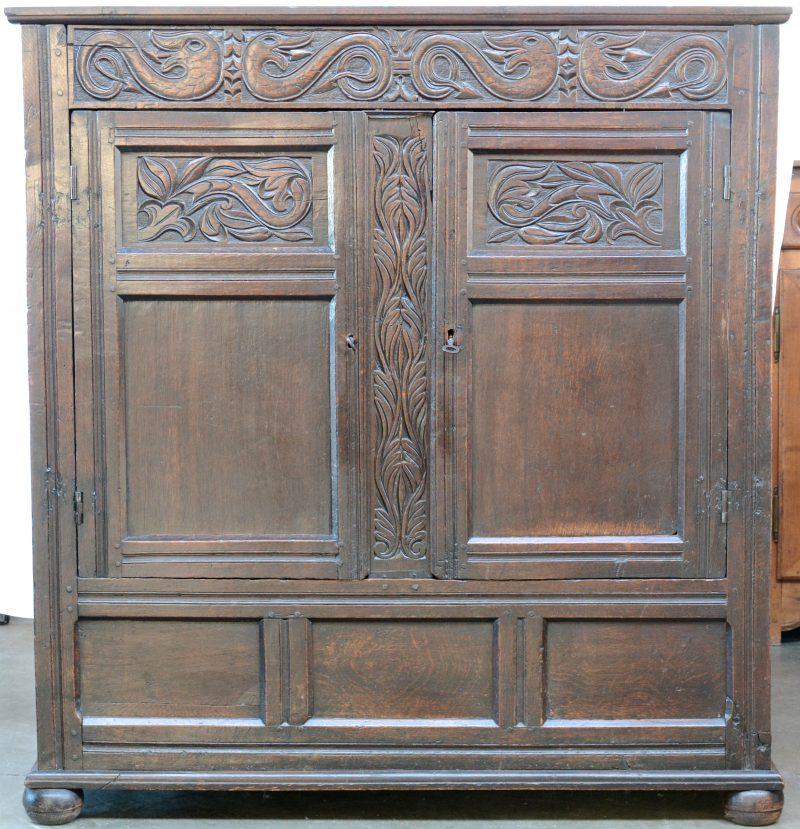 Een eikenhouten tweedeurskast met gesculpteerde panelen. XIXe eeuw.