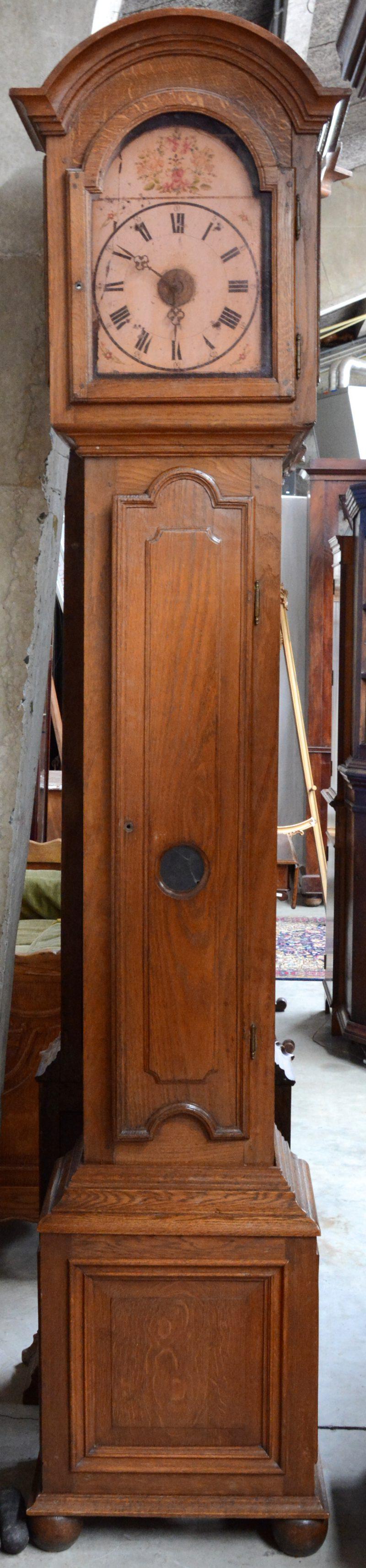 Een staande klok met eikenhouten kast. Het werk met een handbeschilderde houten wijzerplaat met bloemendecor. XIXe eeuw.