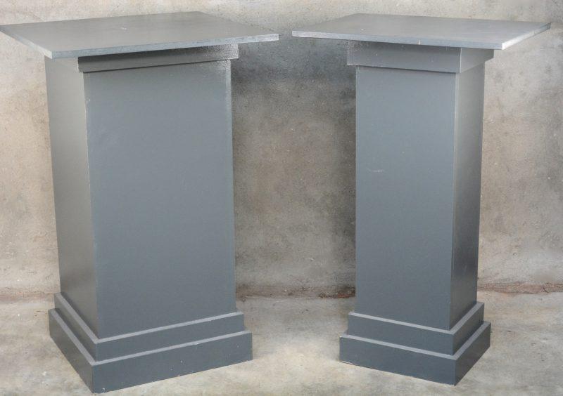 Een smalle en een brede piëdestal van grijsgepatineerd hout.